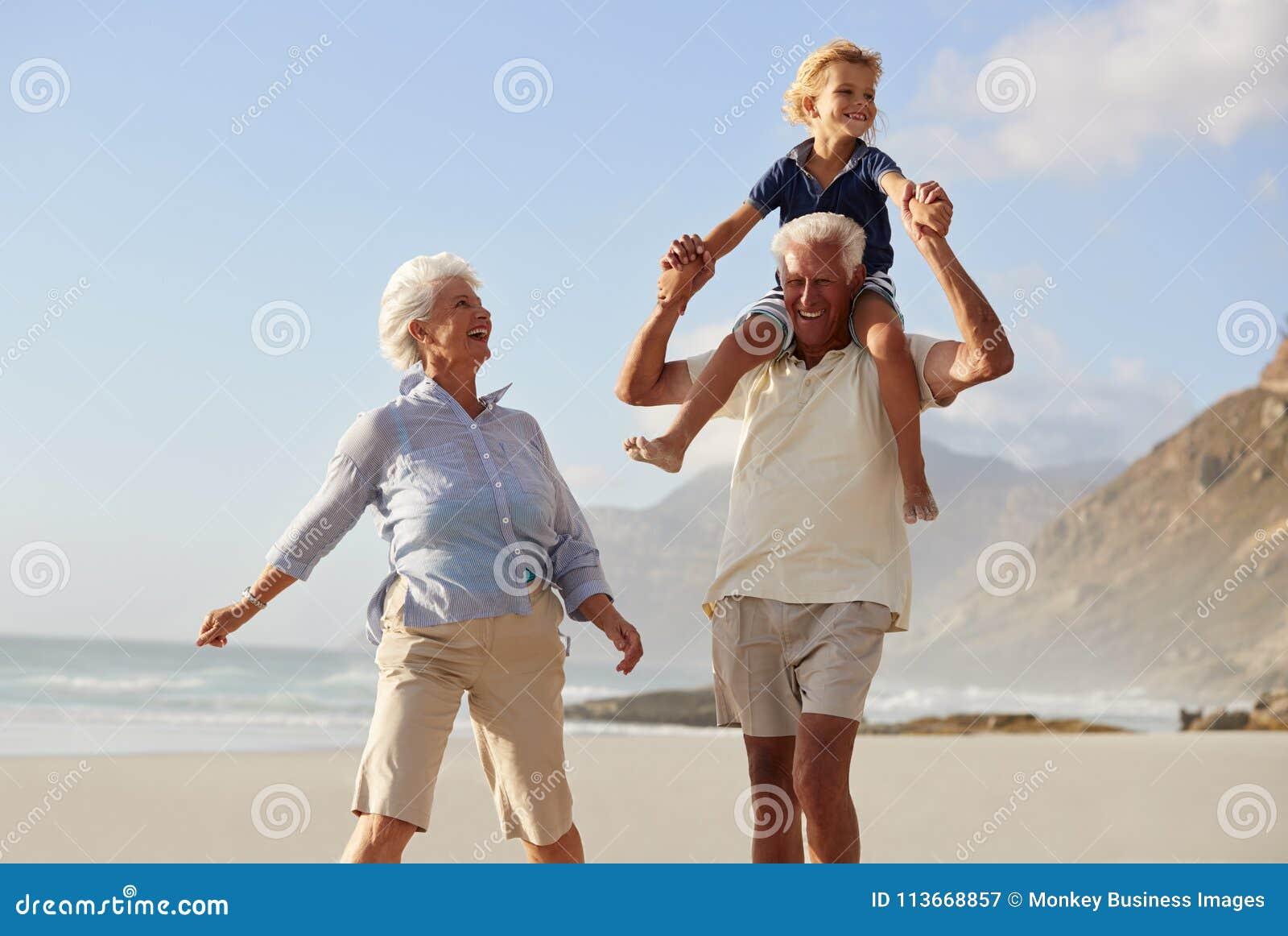 Grands-parents portant le petit-fils sur des épaules sur la promenade le long de la plage