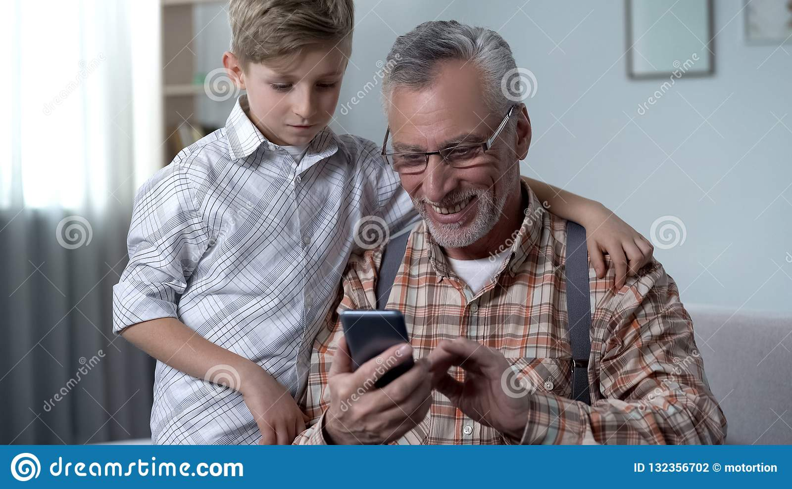 Grandson explaining grandfather how to use smartphone, easy app for elderly