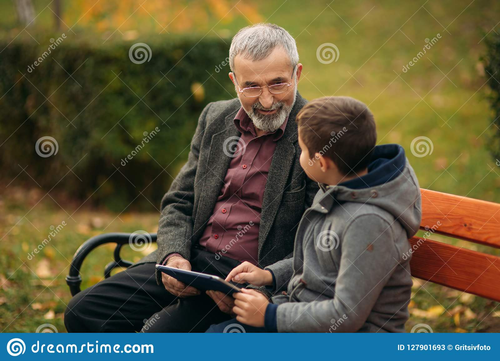 Grandson explains his grandfather how to use tablet. Child help older generation