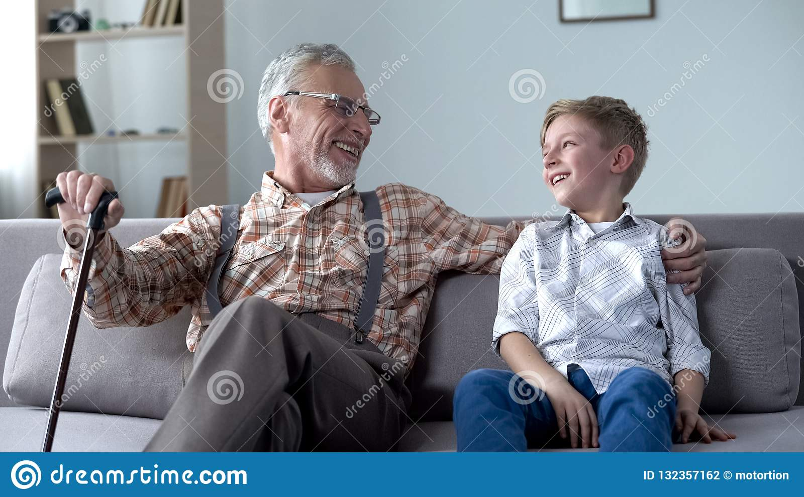 Grandson and grandpa laughing, joking, having good time together, communication