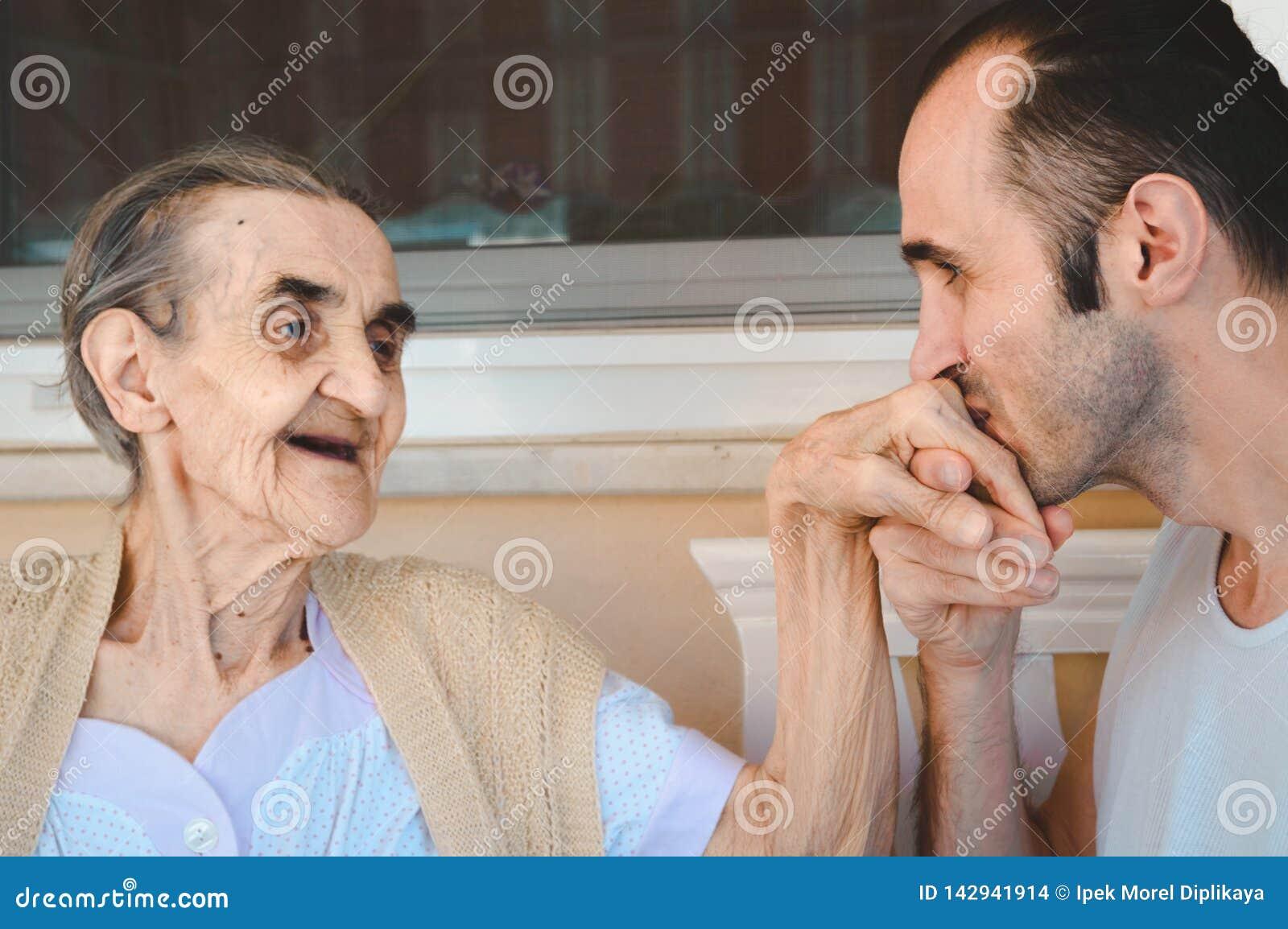 Grandsond całuje jego babci rękę, pokazywać jego miłości i szacunek