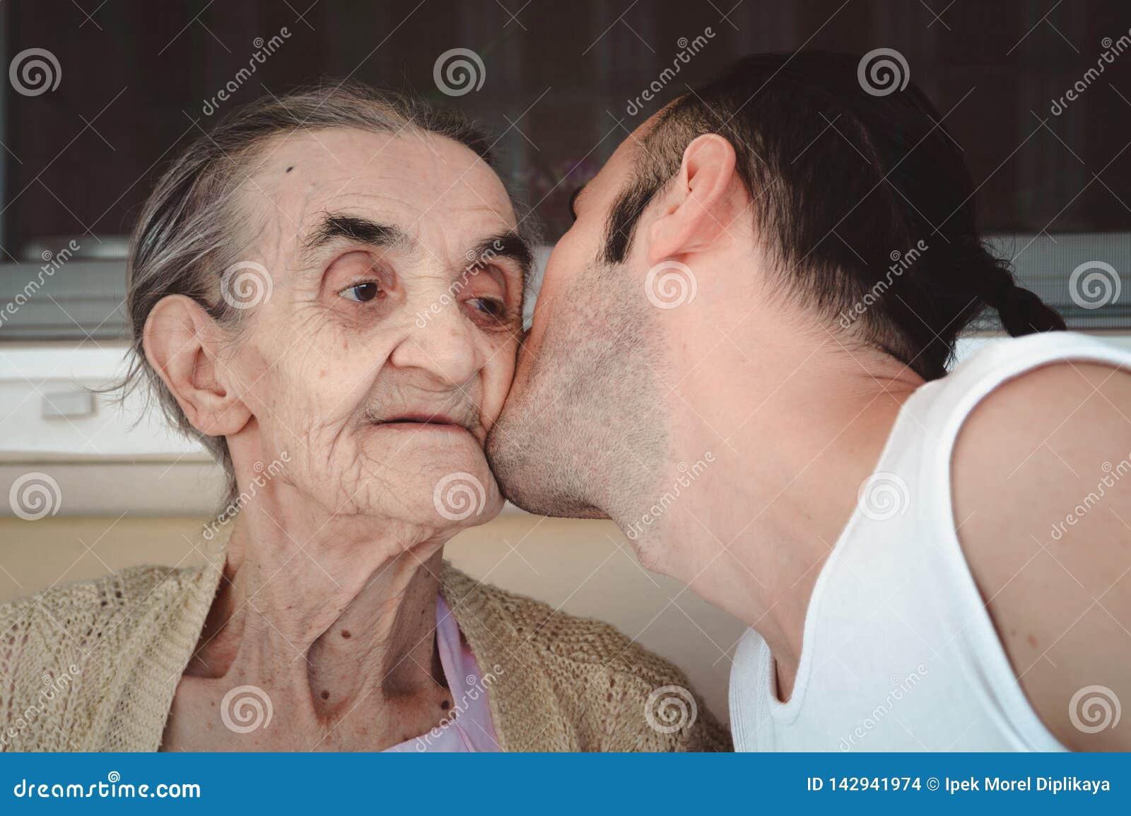 Grandsond embrassant la joue de sa grand-maman, montrant son respect et amour