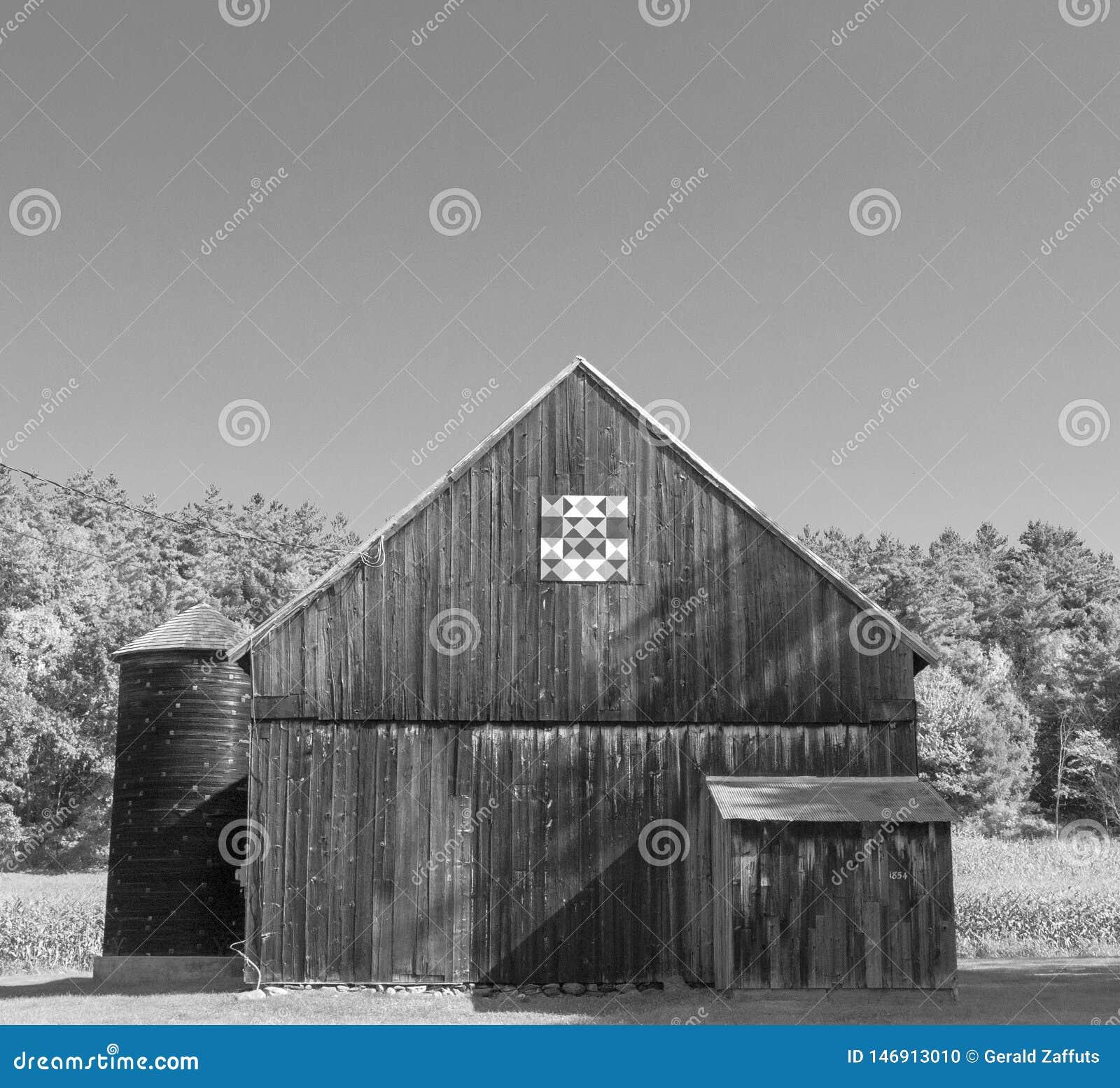 Granero de madera en sol con el edredón