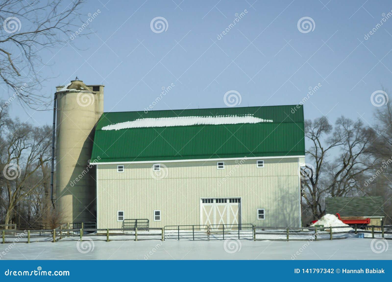 Granero verde blanco grande del tejado con Silo en nieve del invierno