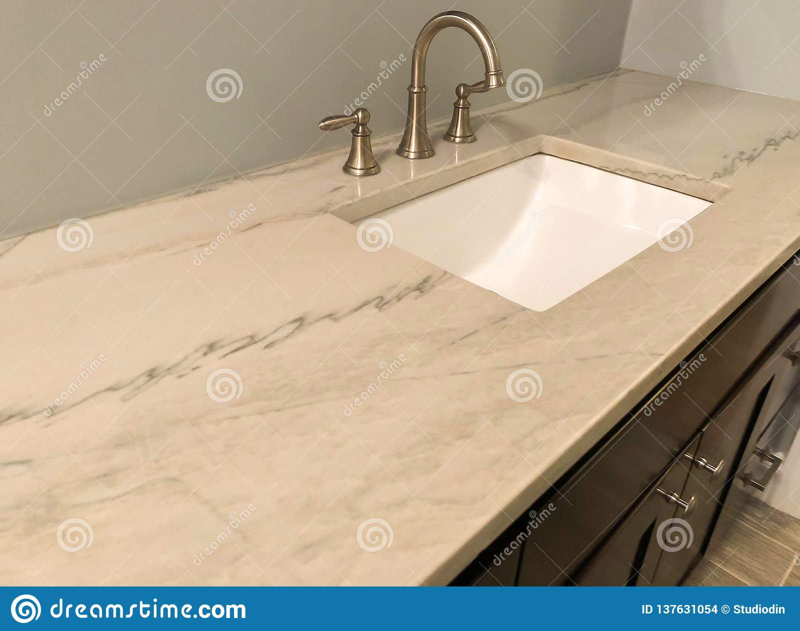 Granite countertop with white sink and chrome faucet on dark wood cabinets, tile floor inside bathroom