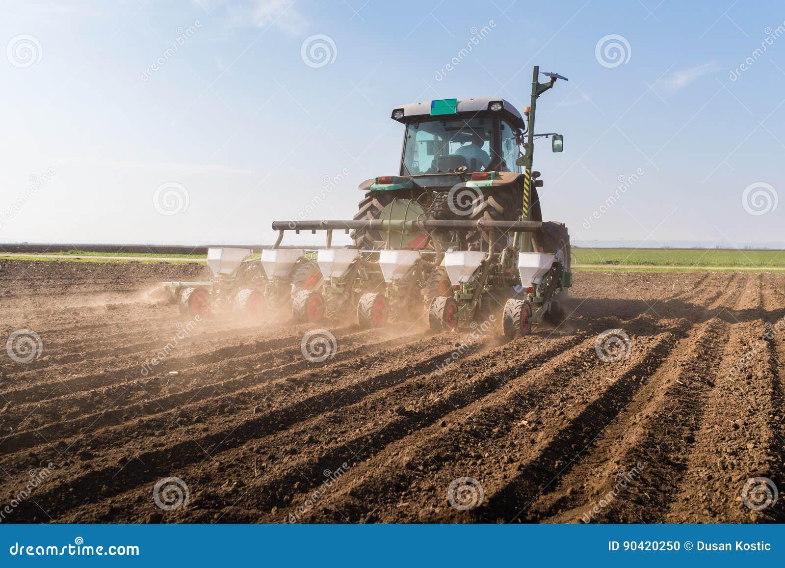Granjero con el sembrador del tractor - la soja de la siembra cosecha en f agrícola