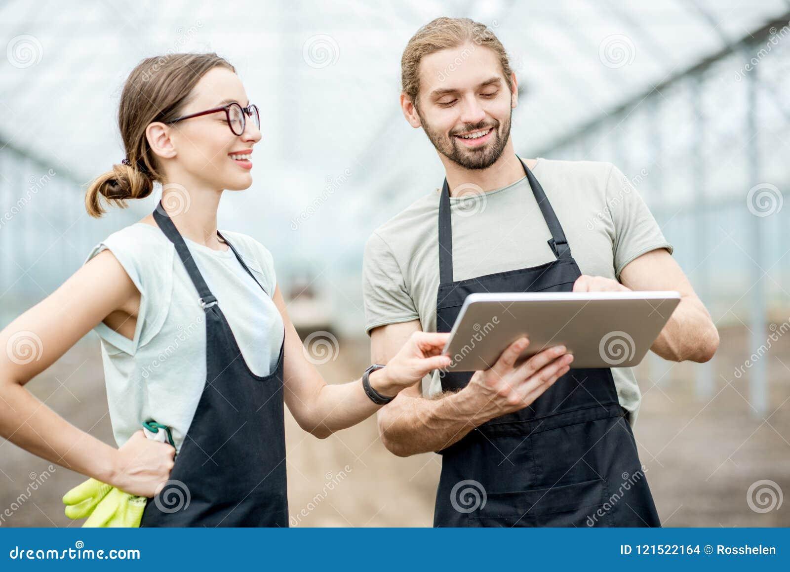 Granjeros con la tableta en el invernadero