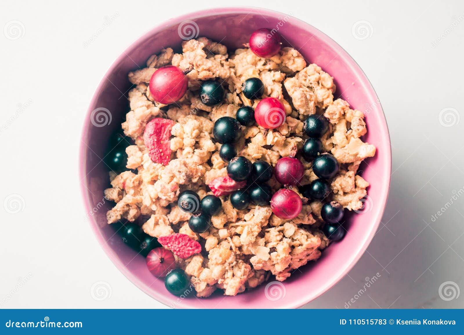 Granola oder Flocken mit Beeren der Schwarzen Johannisbeere und der Stachelbeere in einer rosa Platte auf einem weißen Hintergrun