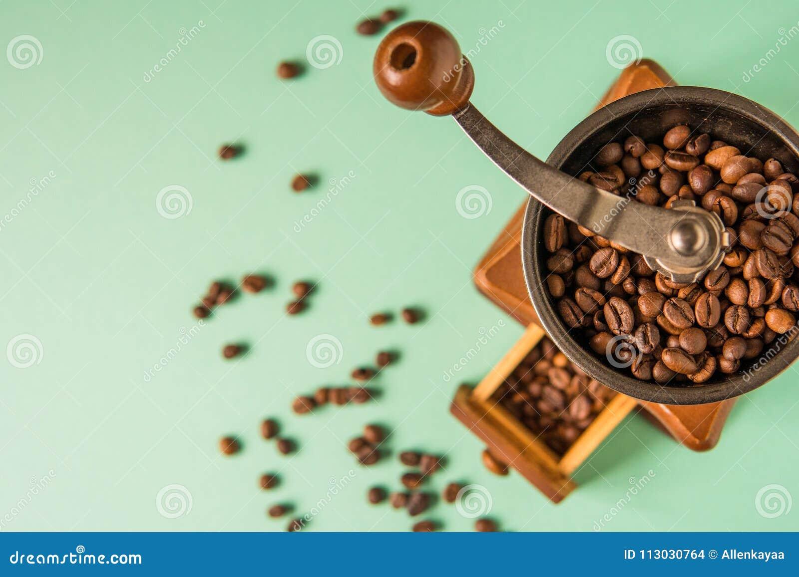 Granos de café en una amoladora de café de mano en un CCB blando del verde