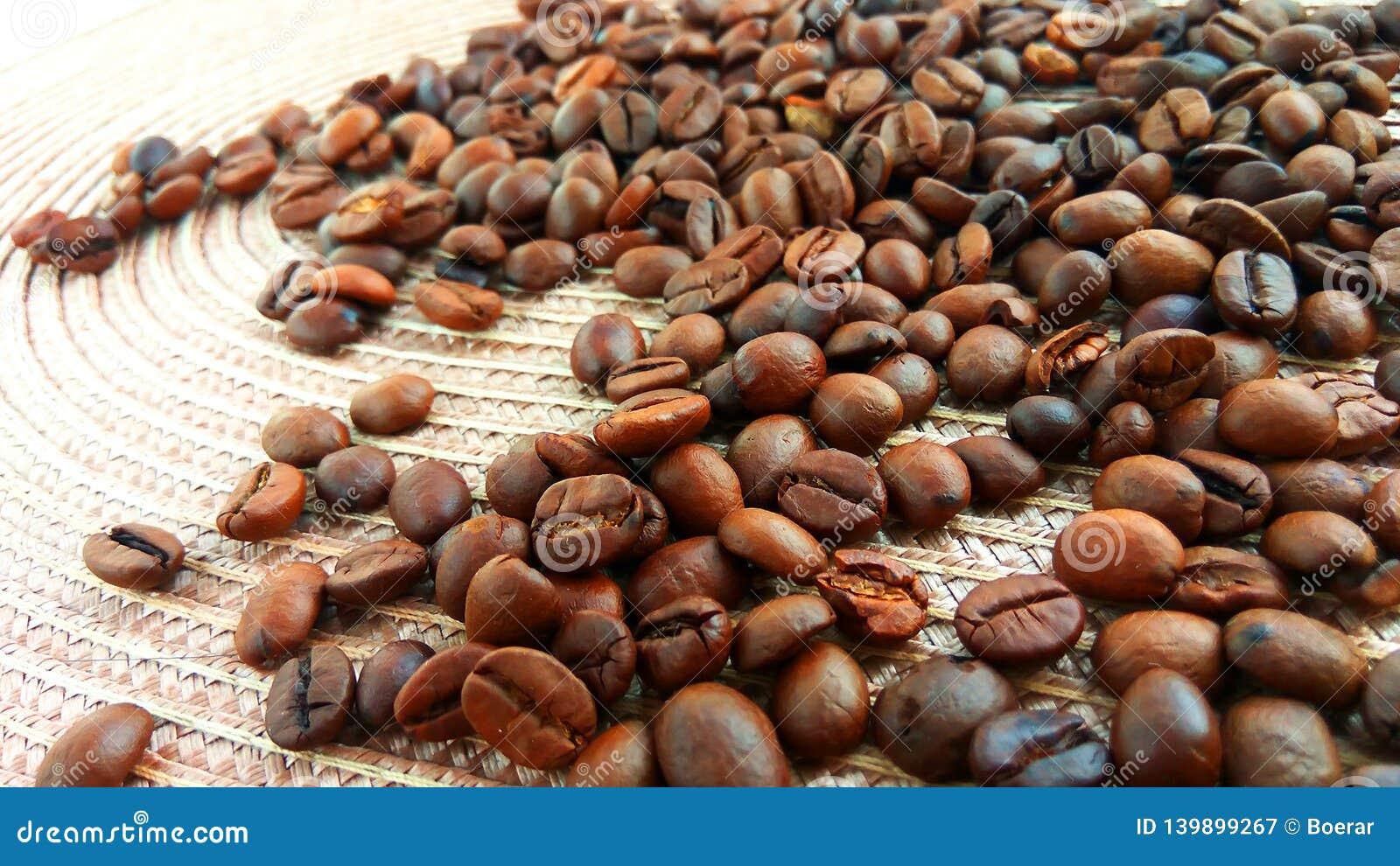 Granos de café marrones asados en el paño ligero de la materia textil