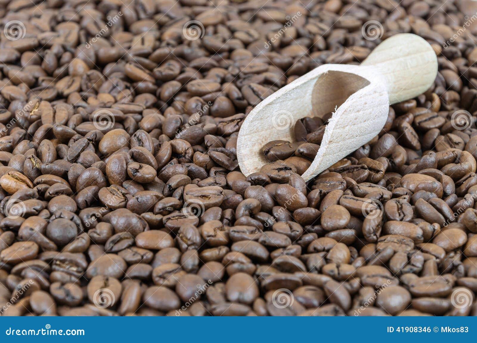 Granos de café y pala de madera