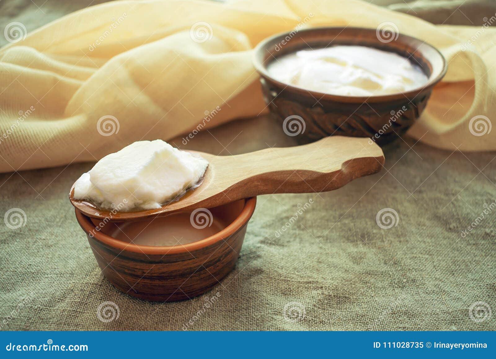 Granos hechos en casa del kéfir de la leche en una cuchara de madera sobre un cuenco o de la arcilla