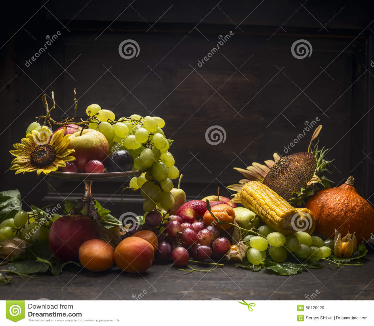 Grape, apples and autumn fruits and vegetables in an iron bowl with a ...