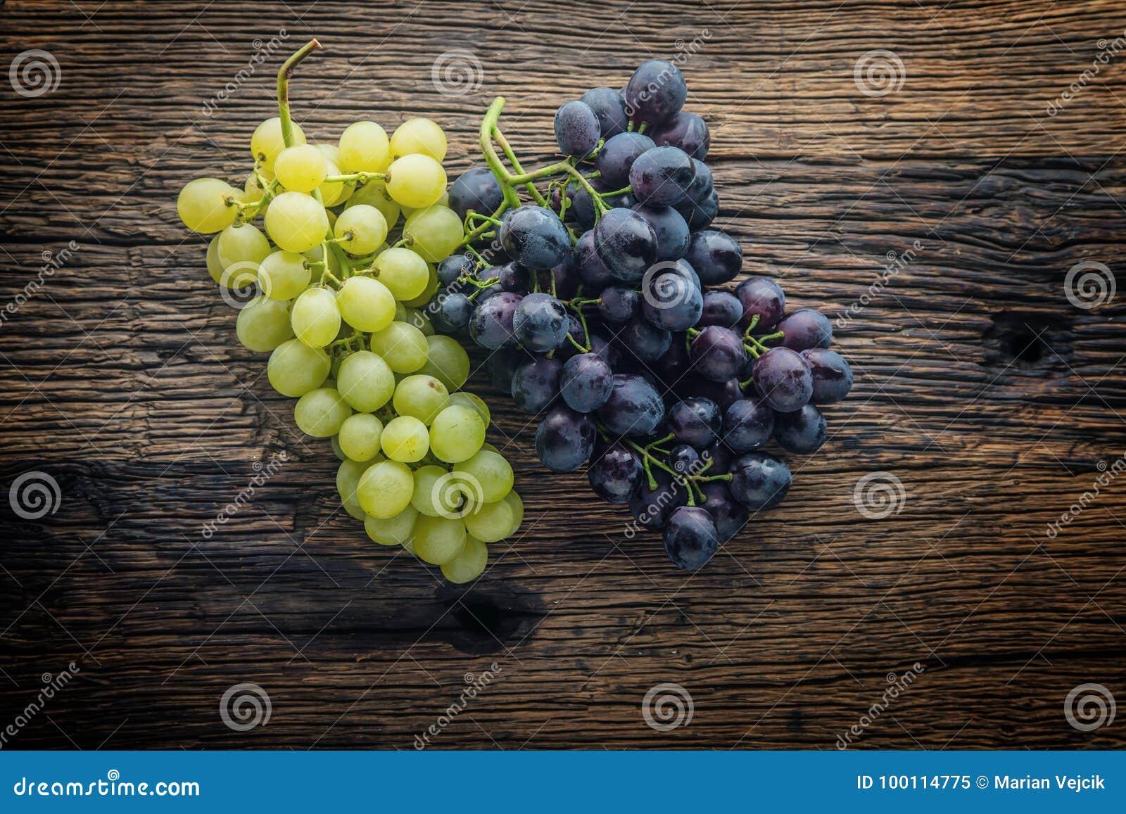 Grapefruits Wiązka stubarwni winogrona na nieociosanym drewnianym stole