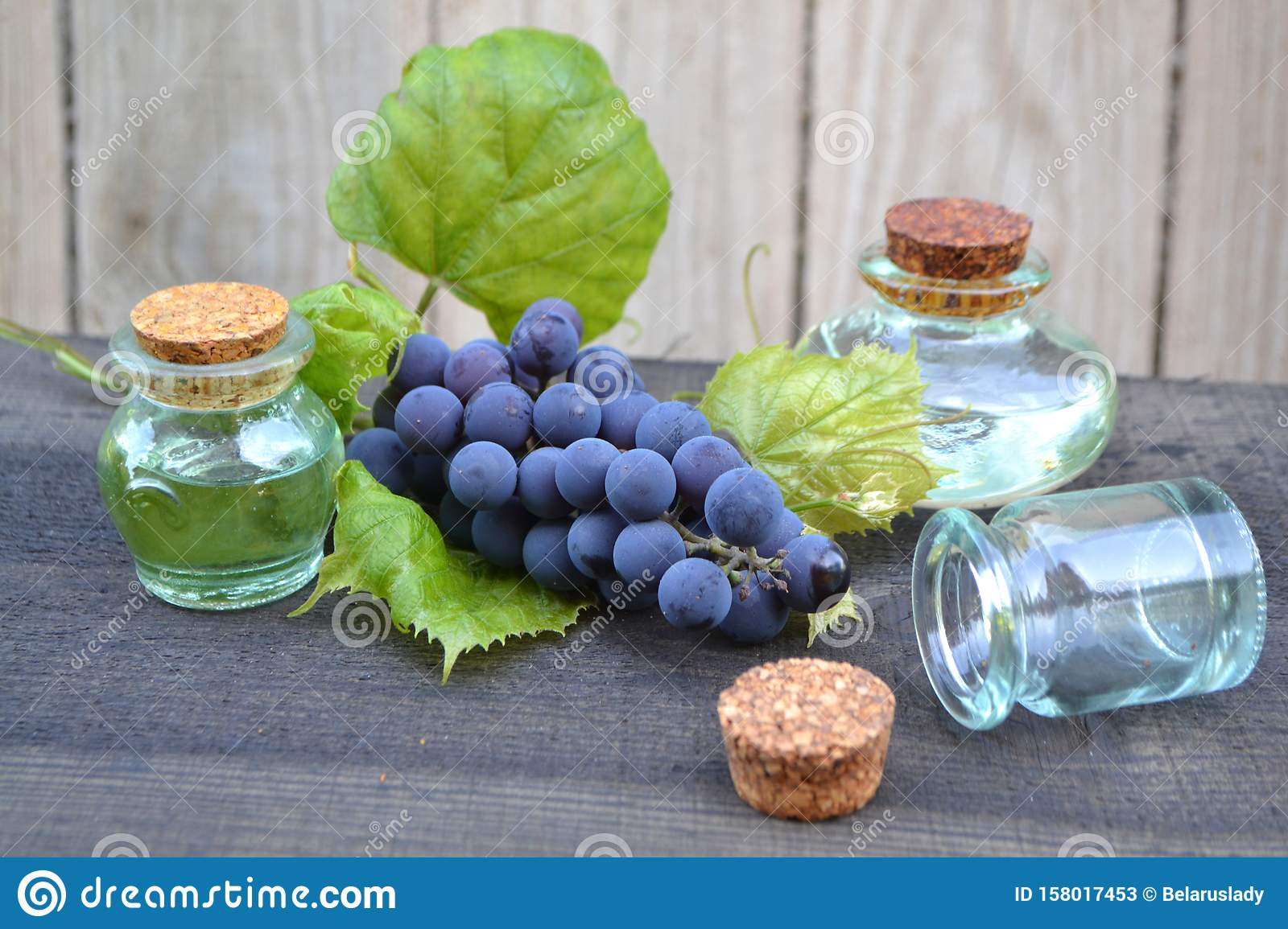 Grapes essential oil in a glass bottle on old rustic wooden boards. Blue grape with green leaves