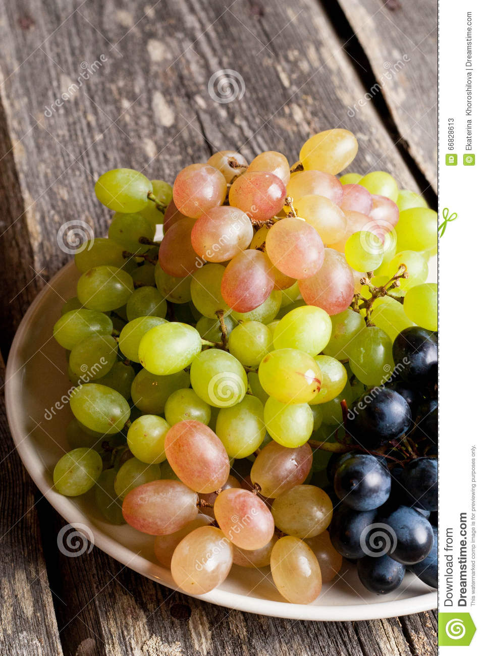 Grapes on a plate on a old wooden table.