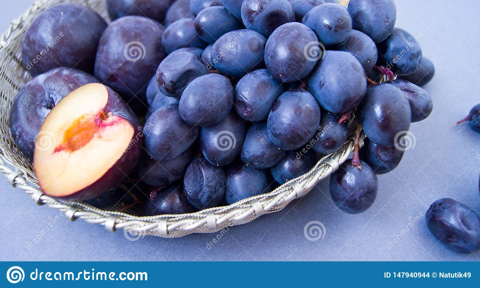Grapes and plums in a silver bowl