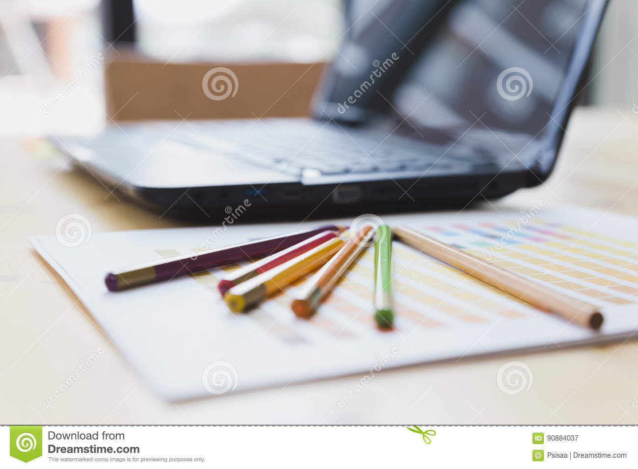 graphic designer desk table with computer, crayon and color guide palette swatches