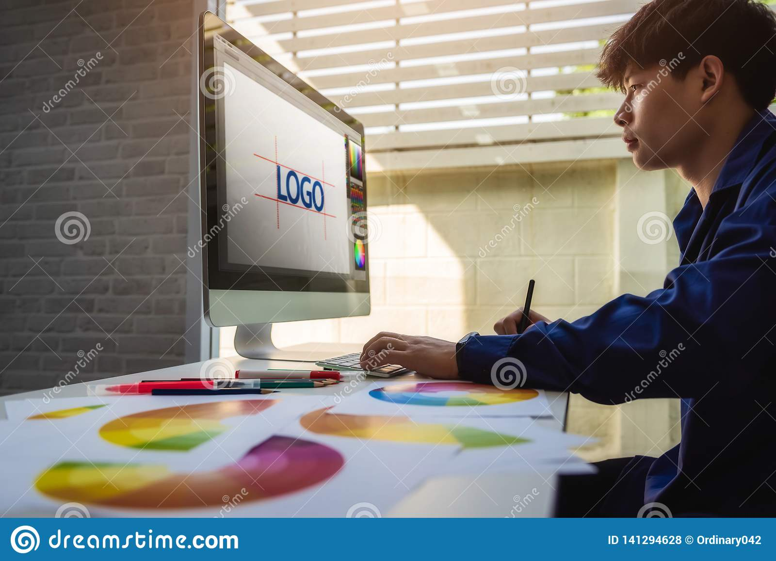 Graphic designer man creative using Color swatch samples for website layout and application for mobile phone in workplace