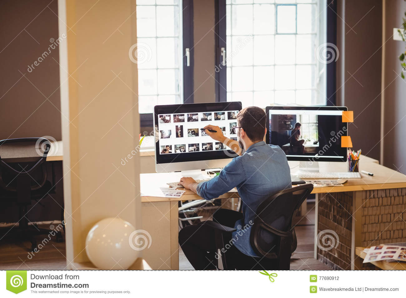 Graphic Designer Working At His Desk In Office