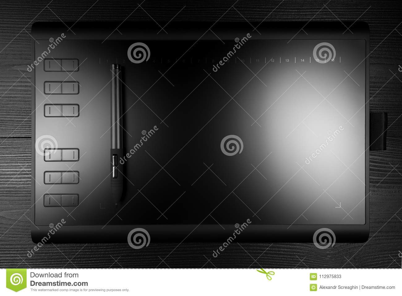 Graphic tablet with pen for illustrators and designers on black wooden background.