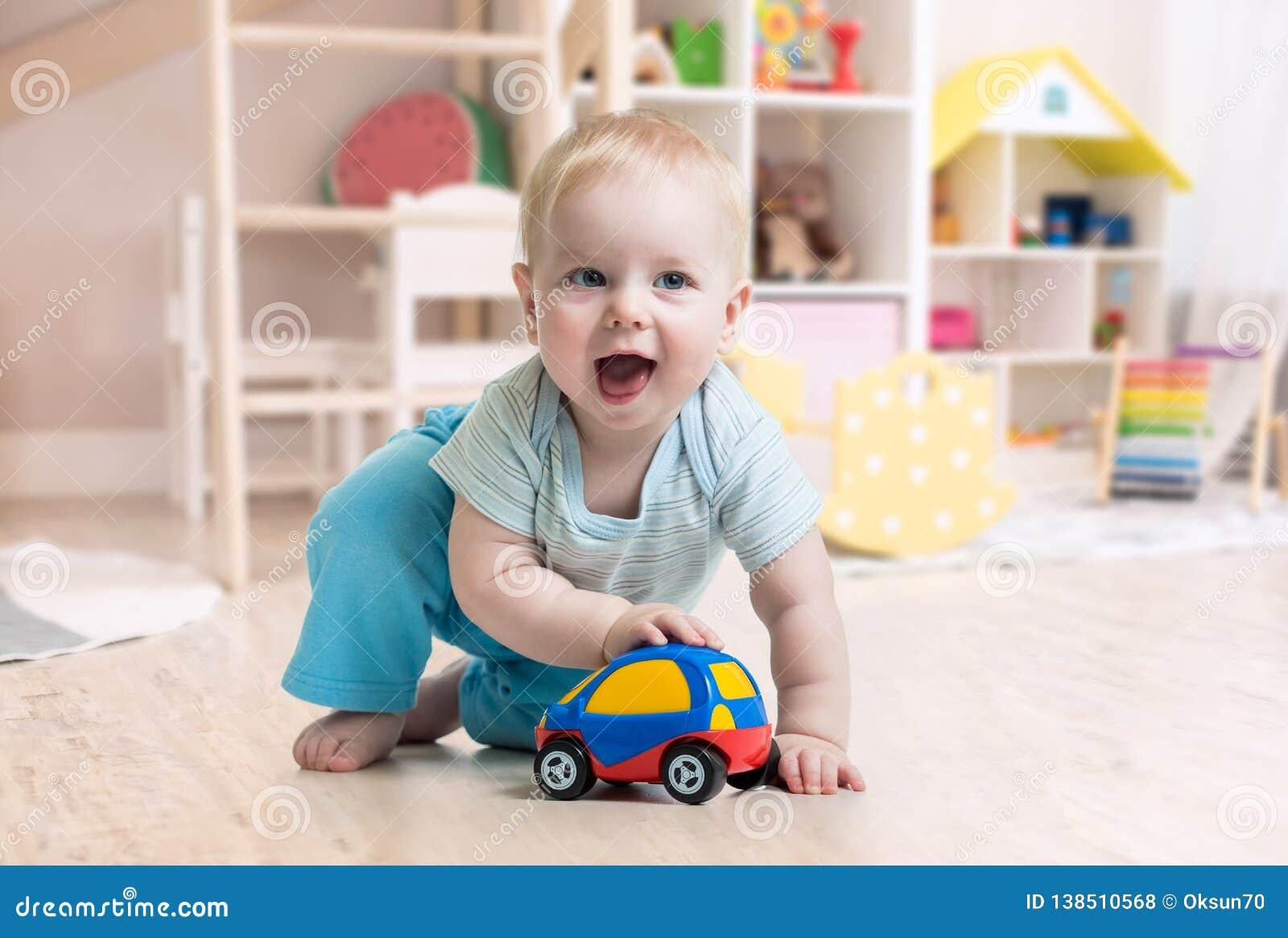 Grappig babyjongen het spelen stuk speelgoed in kinderdagverblijf