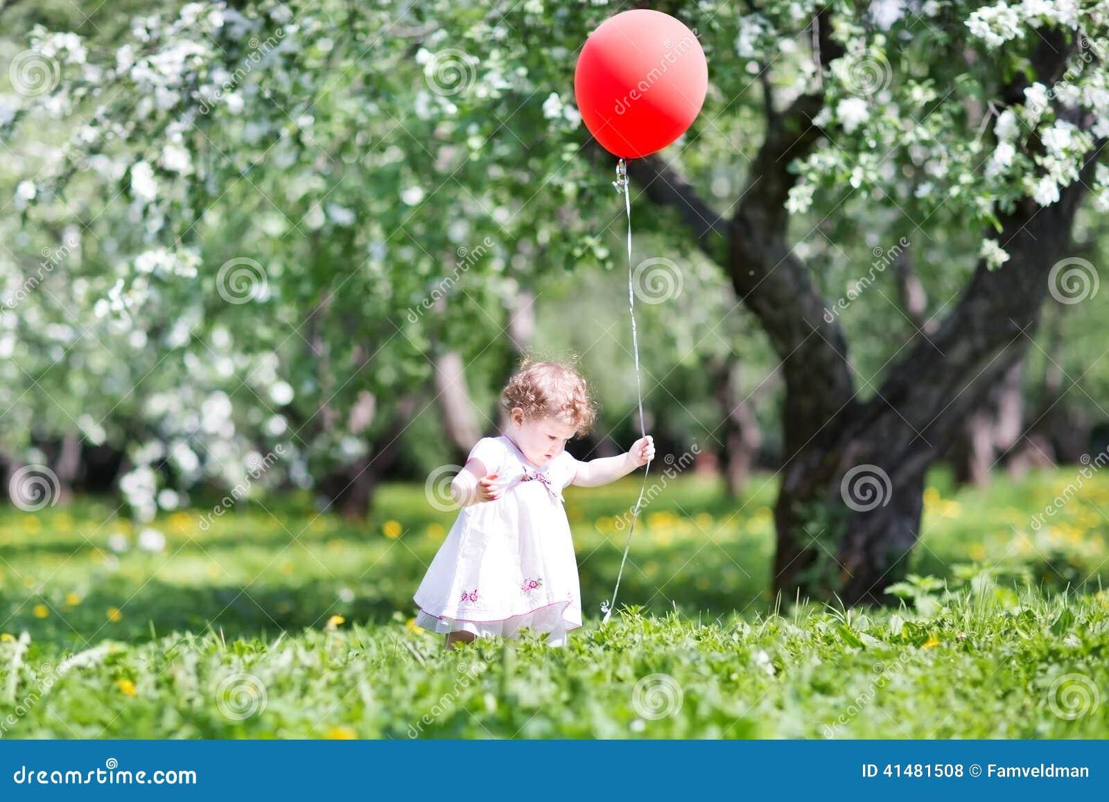 Grappig babymeisje in de tuin van de appelboom met rode impuls