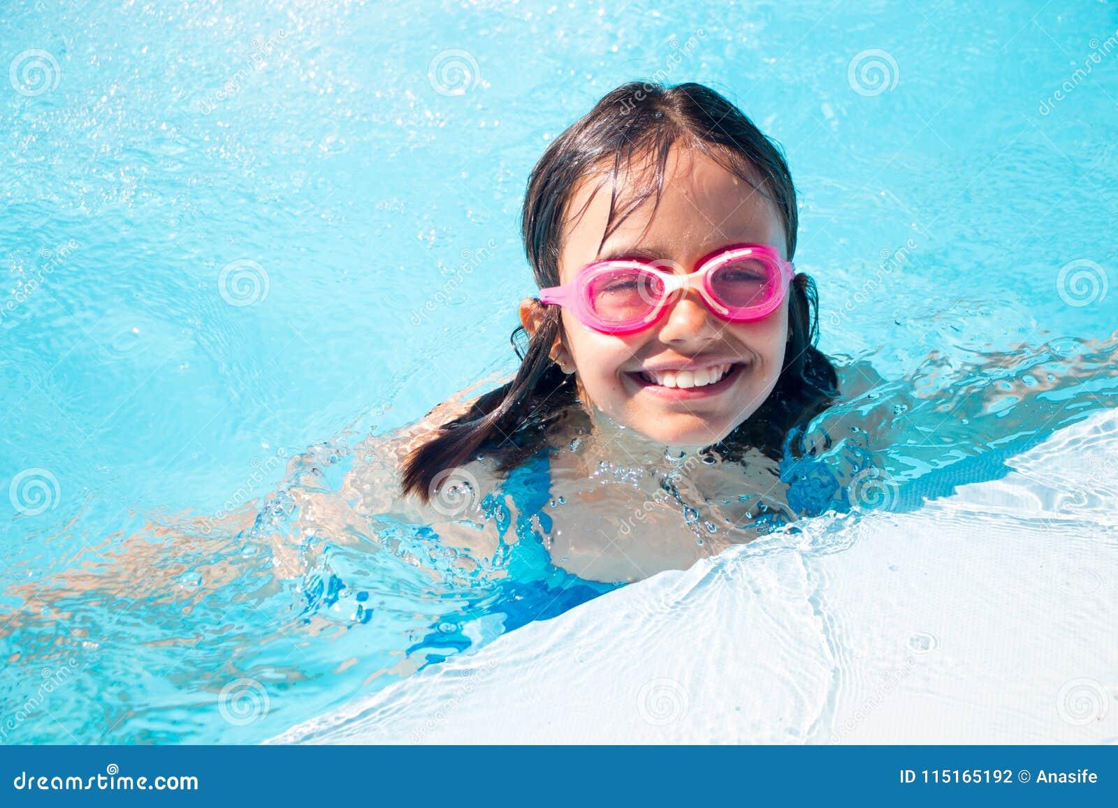 6cde5c84e58b8d Gelukkig meisje met beschermende brillen die in de pool zwemmen openlucht