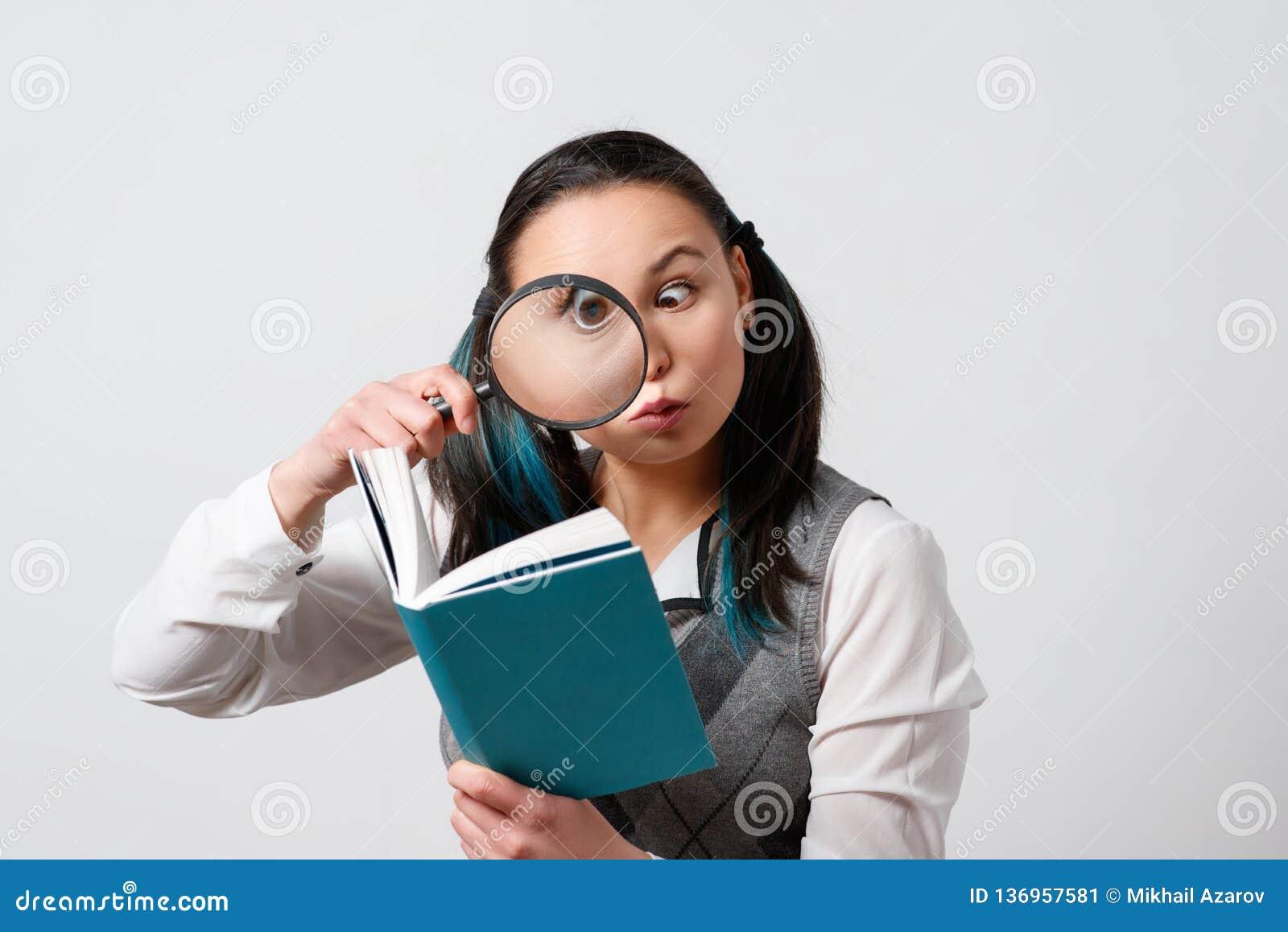 Grappig meisje die een boek door een vergrootglas bekijken Op een grijze achtergrond