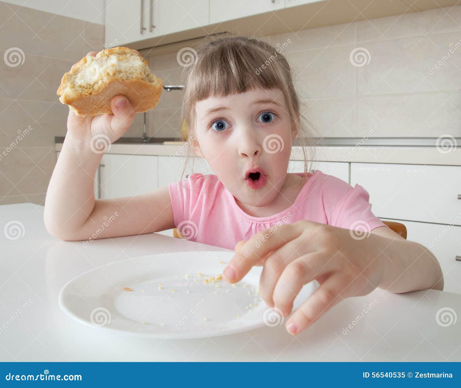 Grappig meisje die in verbazing met wijd open ogen kijken en een pastei houden stock foto - Ogen grappig ...
