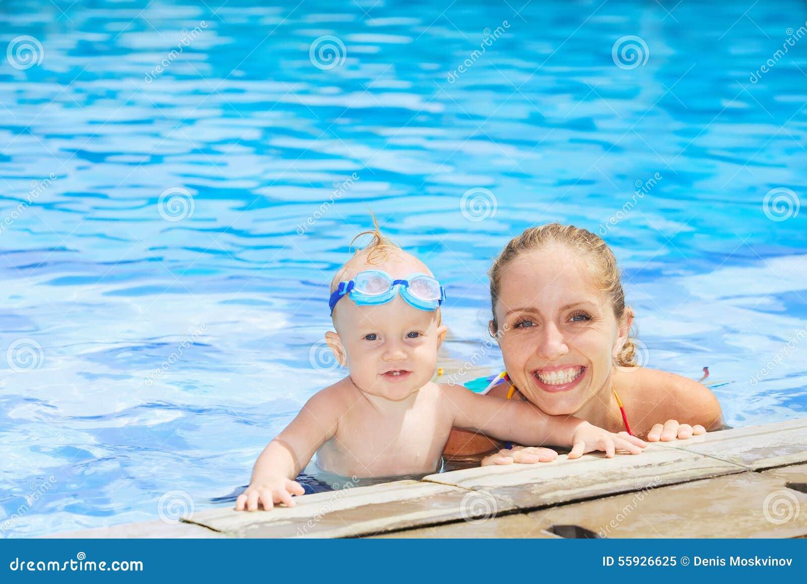 Grappig portret van babyjongen het zwemmen met moeder in pool