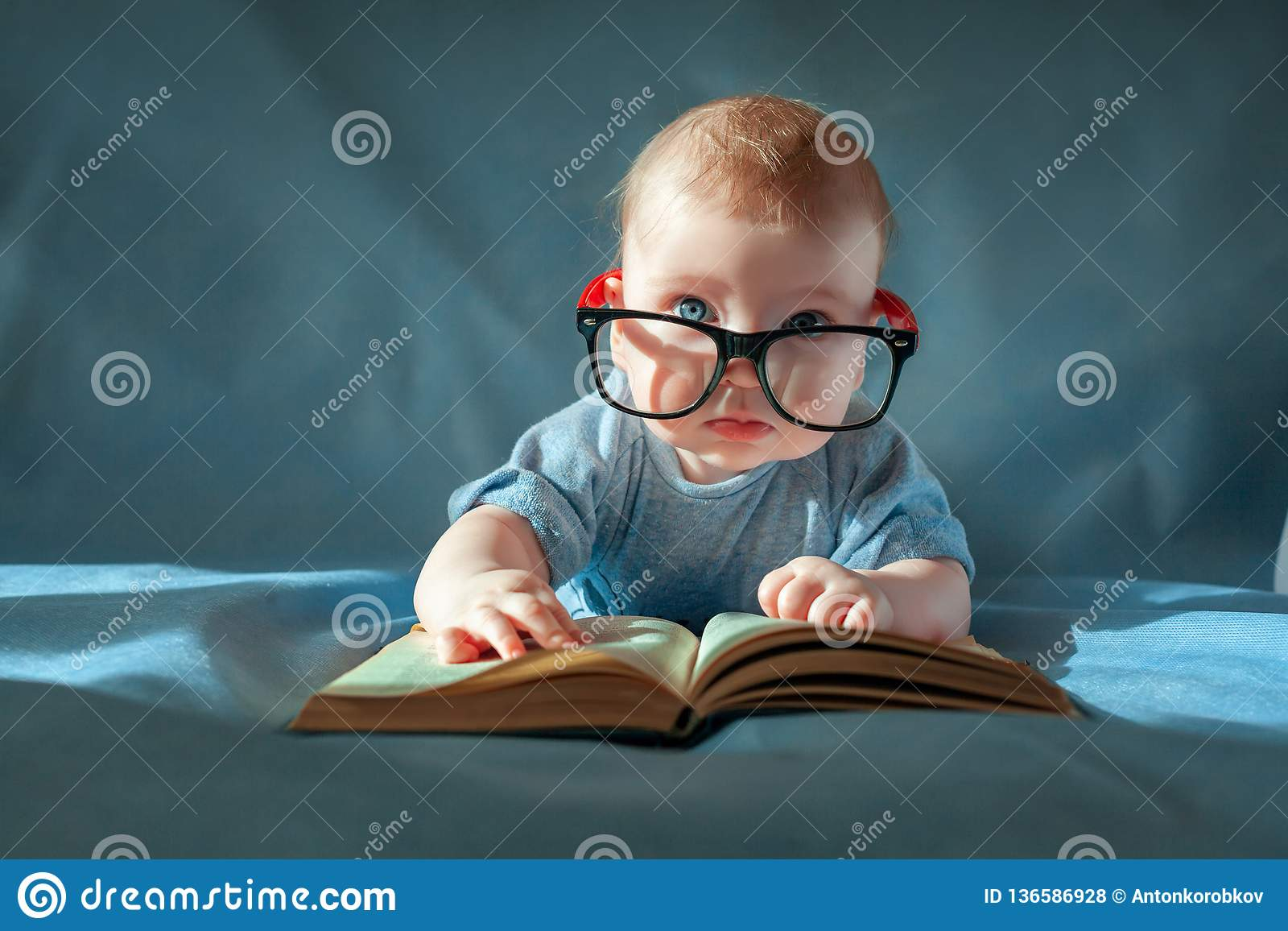 Grappig portret van leuke baby in glazen De baby ligt op zijn maag en leest een oud boek op een blauwe achtergrond