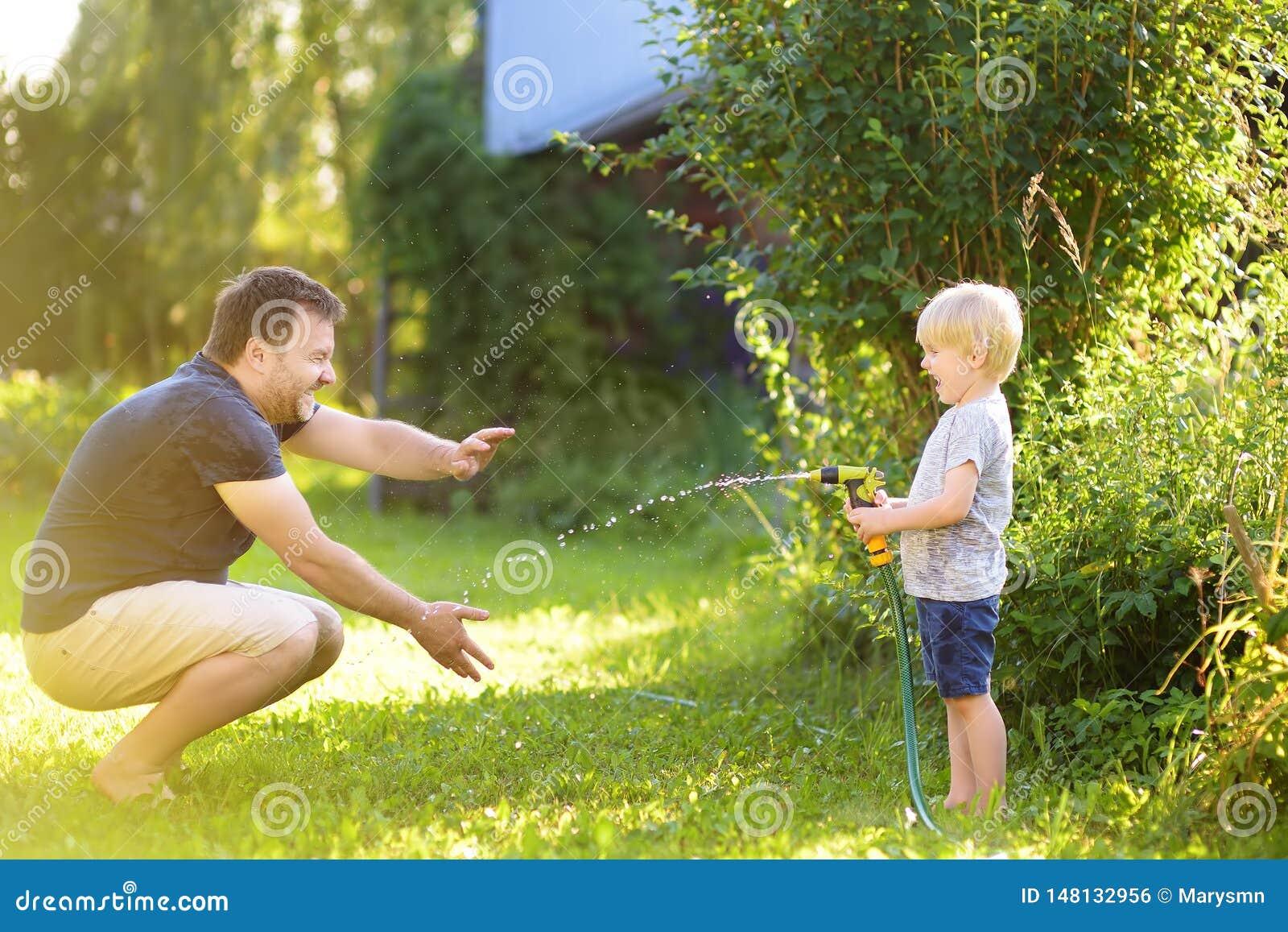 Grappig weinig jongen met zijn vader die met tuinslang spelen in zonnige binnenplaats Kleuterkind die pret met nevel van water he