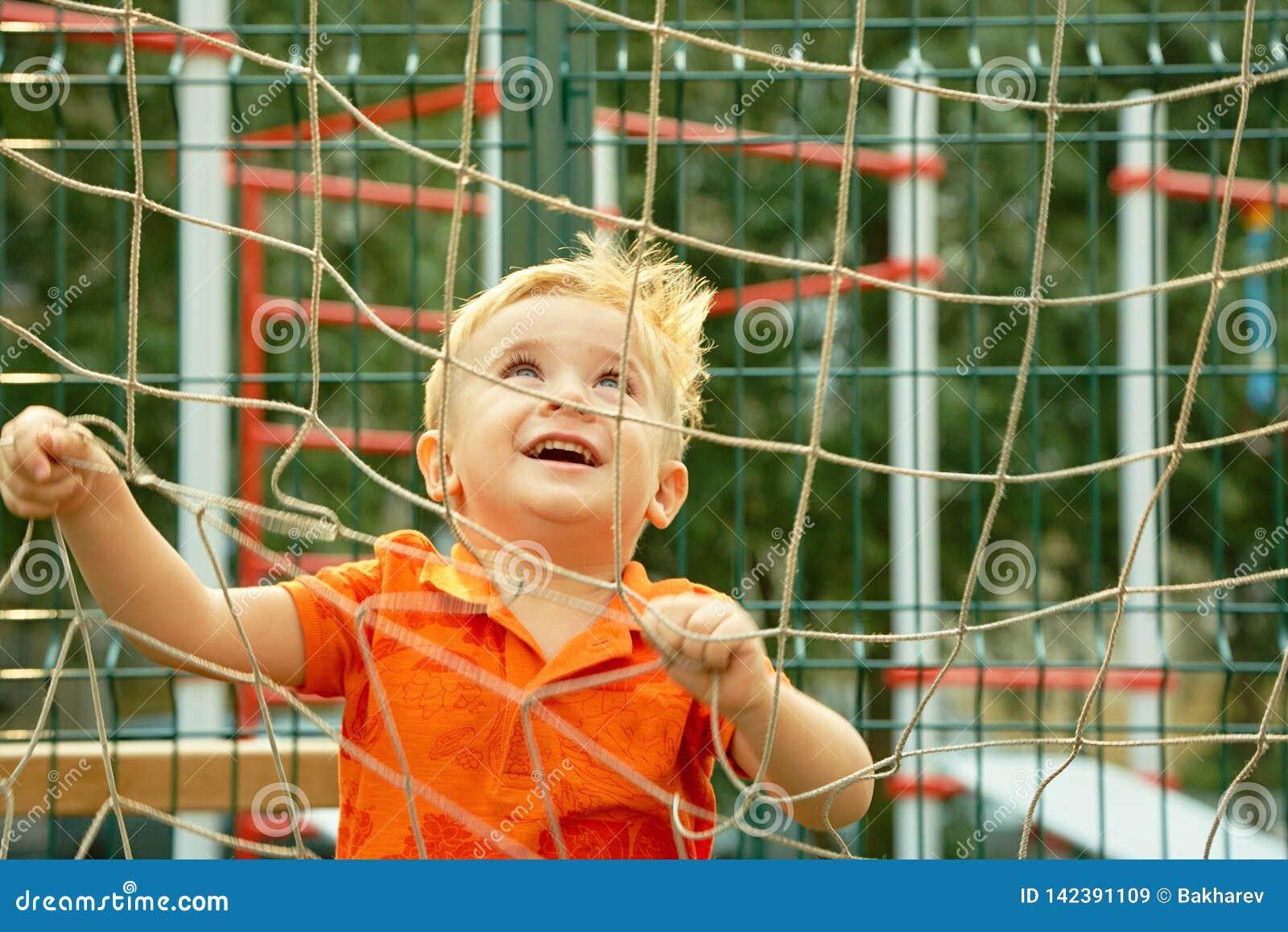 Grappig weinig jongen op speelplaats met net van voetbalpoort speelkind op sportengrond