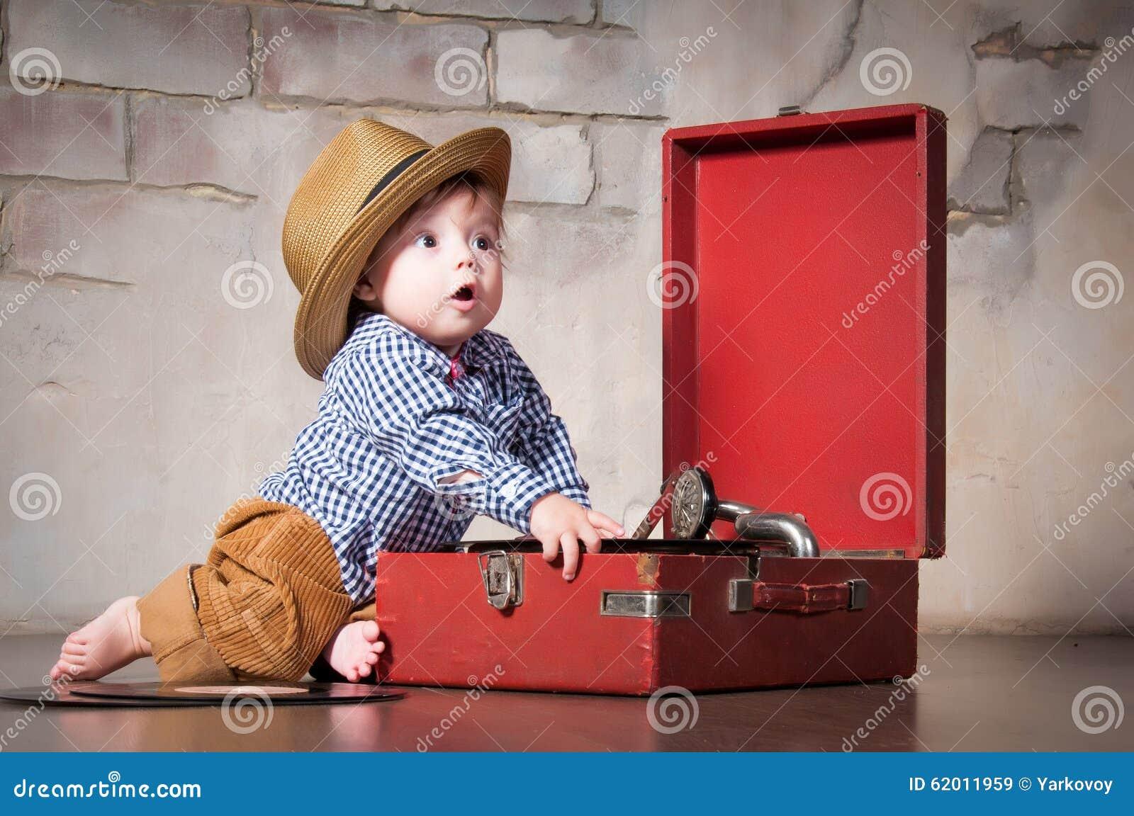 Grappige babyjongen in retro hoed met vinylverslag en grammofoon