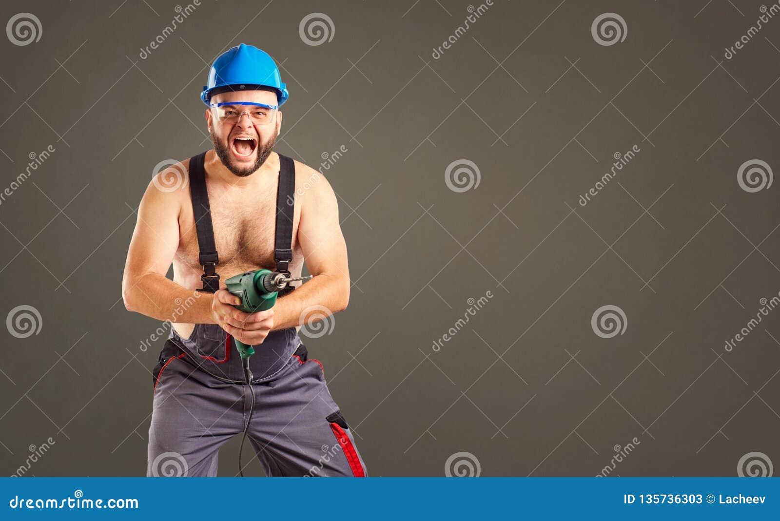 Grappige bouwer met een boor in zijn handen