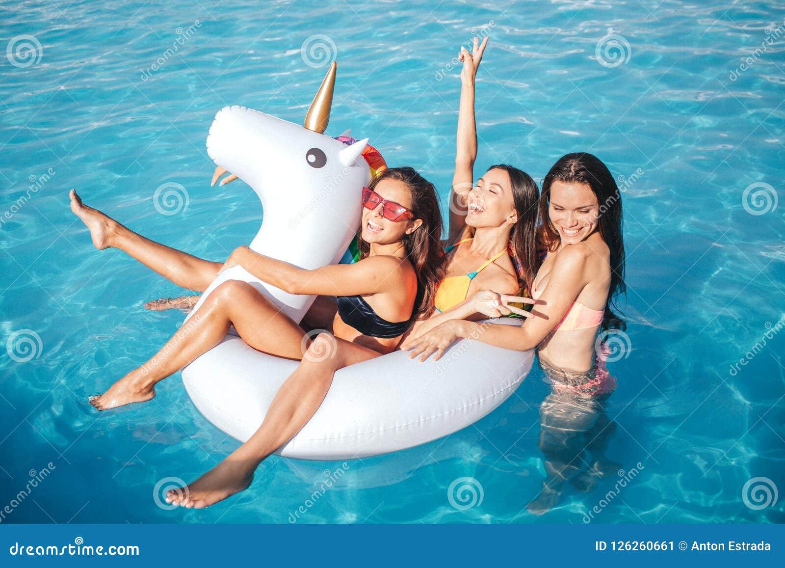 Grappige en schitterende jonge vrouw die in pool zwemmen Zij spelen met witte vlotter Twee modellen zijn daar Derde men is eracht