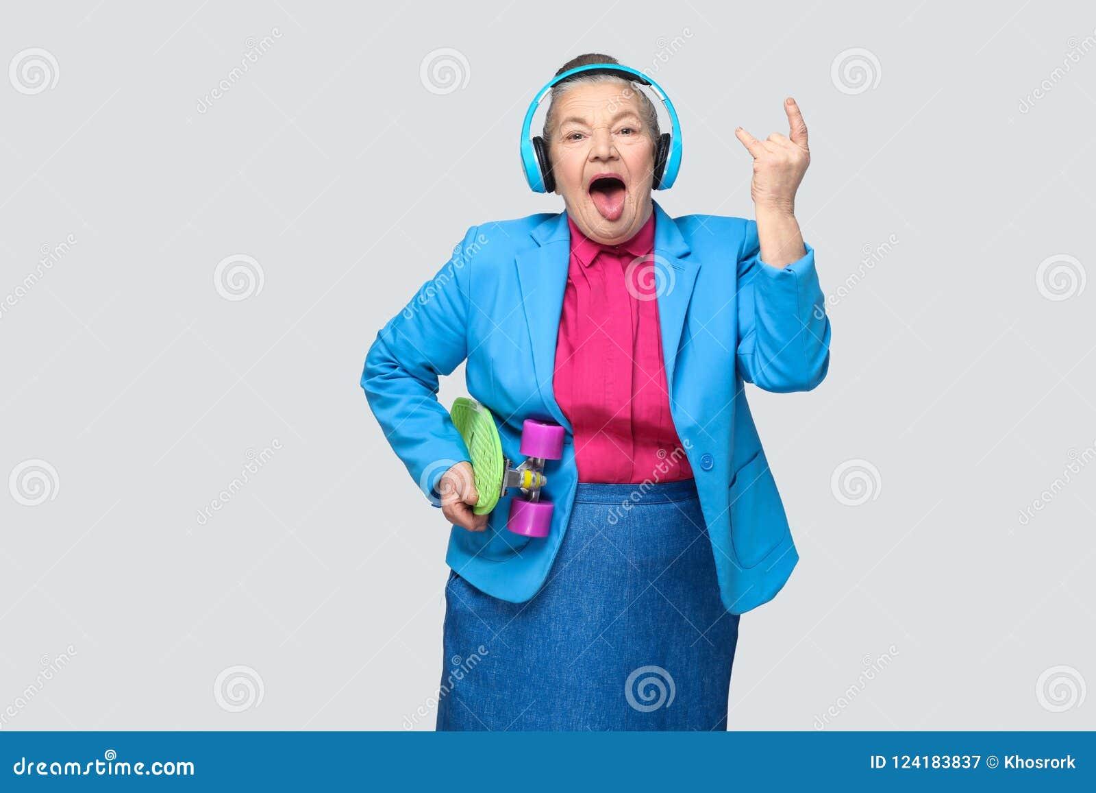 In grappige grootmoeder in toevallige stijl met blauwe hoofdtelefoons ho