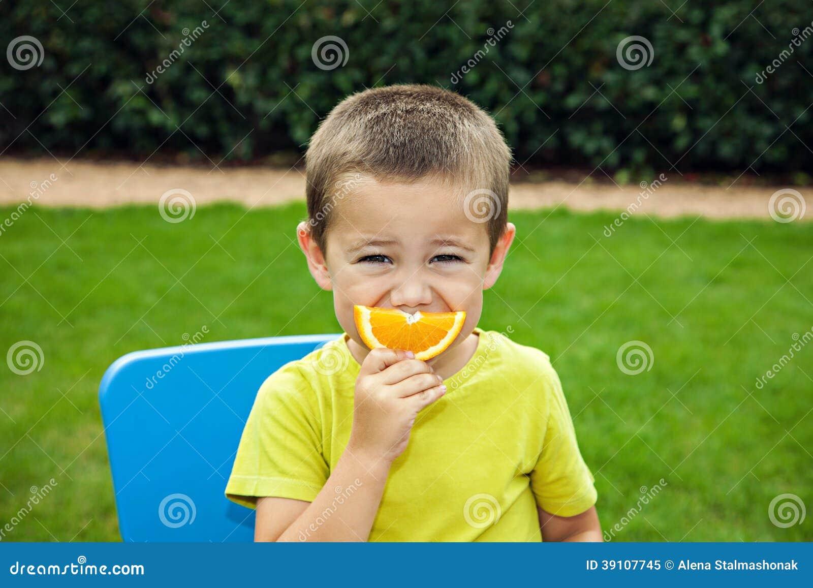 Grappige jongen met sinaasappel