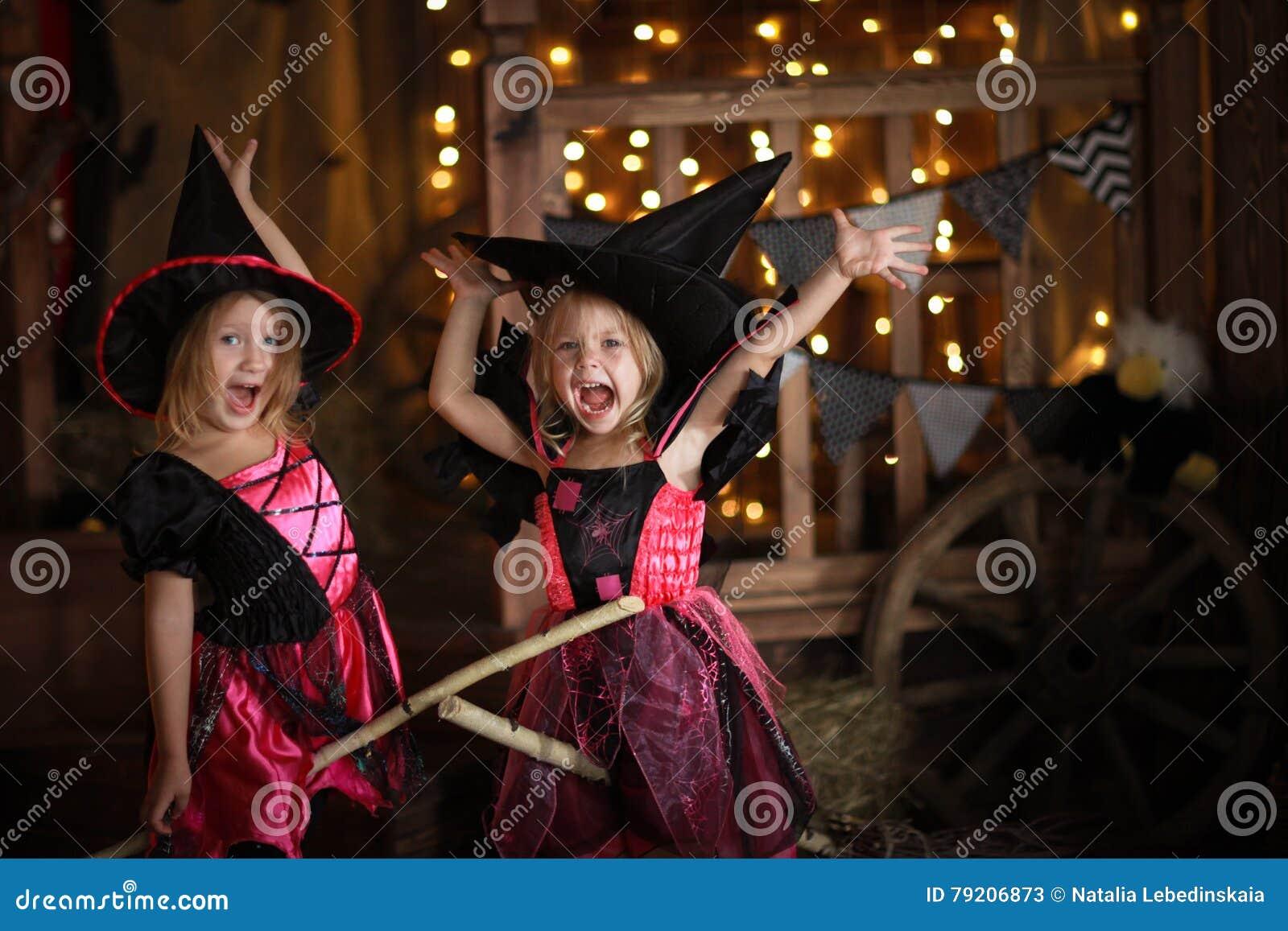 Grappige kinderenmeisjes in heksenkostuum voor donkere backg van Halloween
