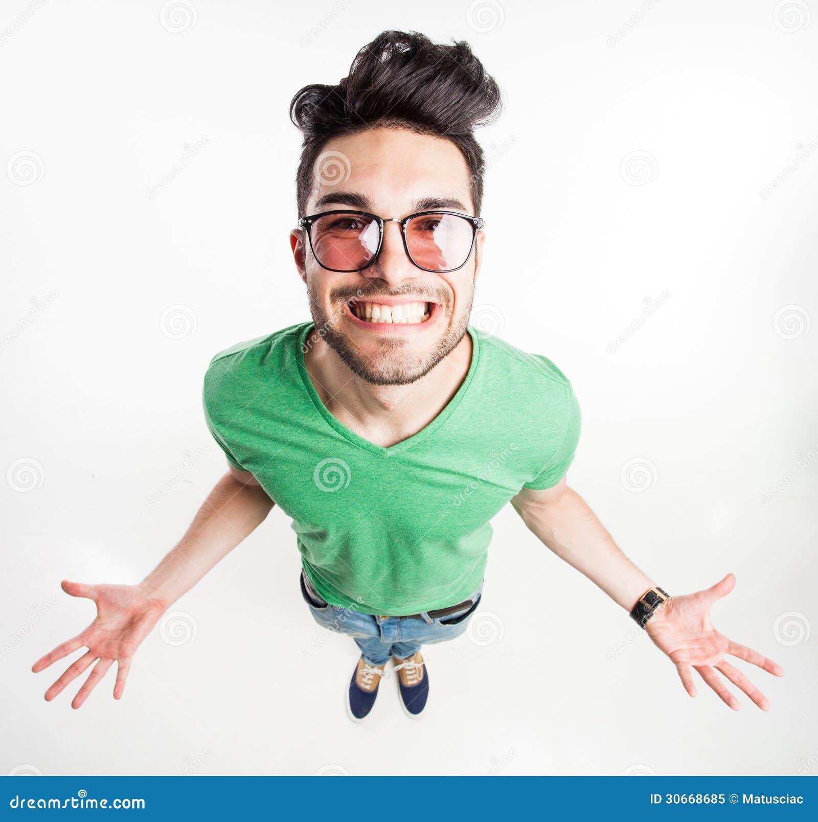 Grappige knappe mens met hipsterglazen die zijn grote palmen en glimlachen tonen - breed hoekschot