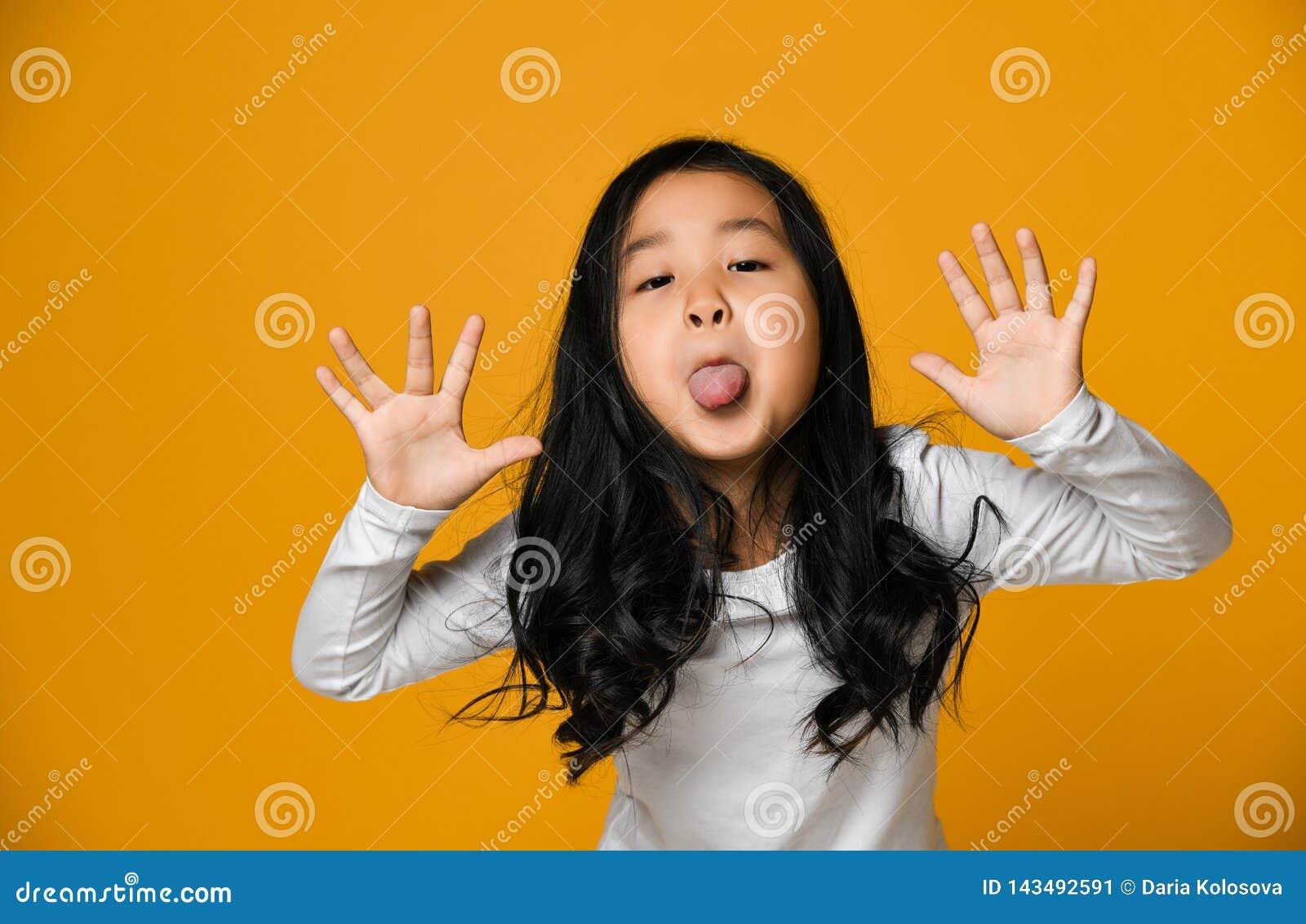 Grappige leuk weinig Aziatisch meisje toont de tong