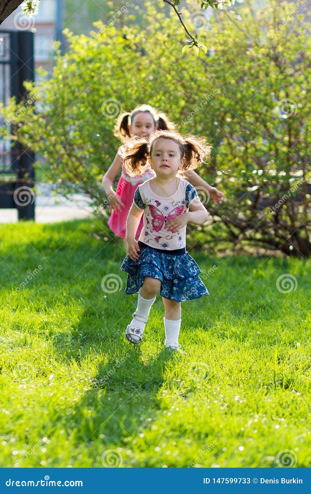 Grappige meisjes die op het gazon met haar moeder lopen De zusters spelen samen met mamma Moeder Zorg Gelukkige Familie