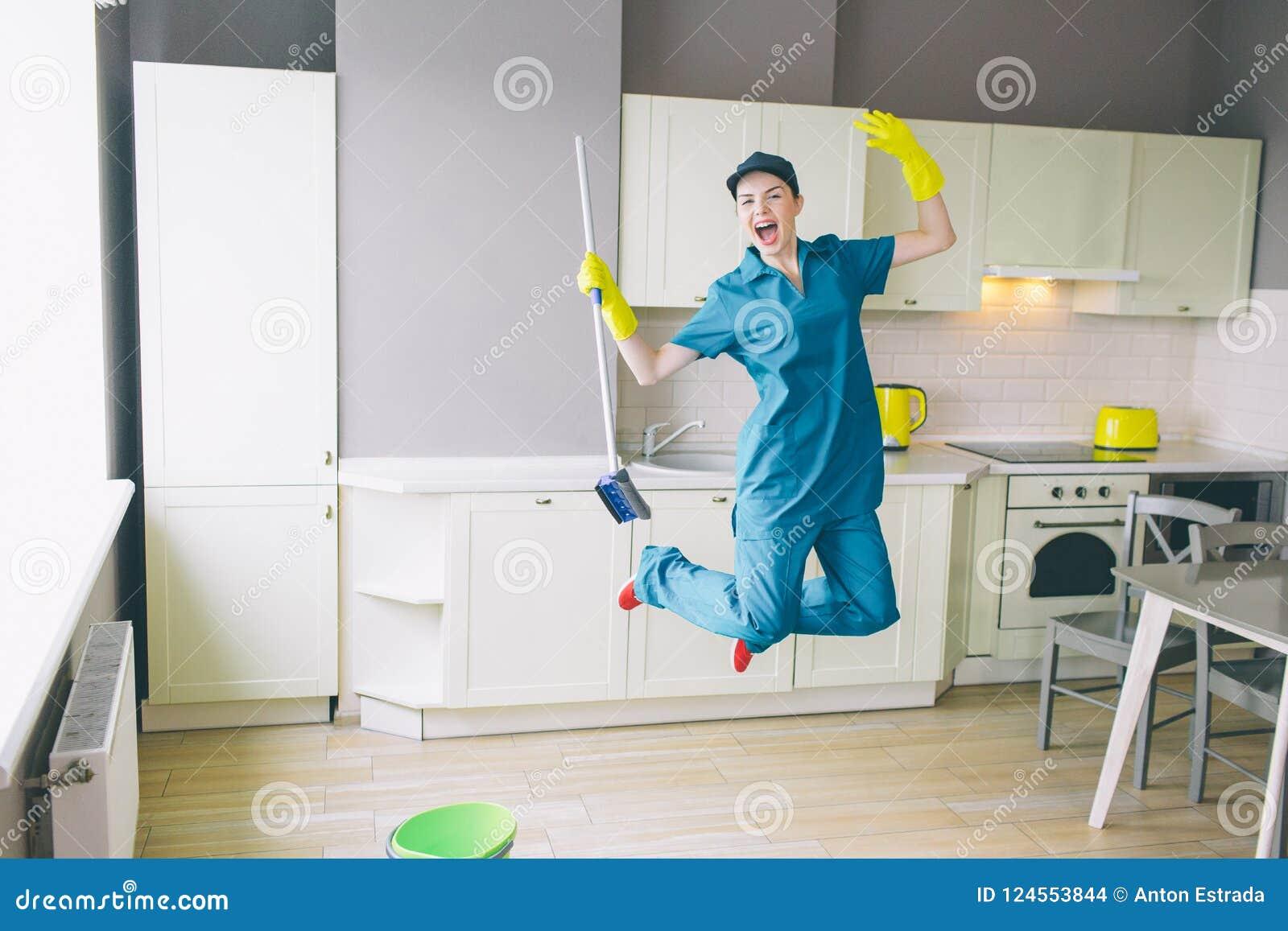Grappige schonere sprongen omhoog in keuken Whe houdt omhoog haar handen Het meisje heeft rust die zij heeft opgehouden schoonmak
