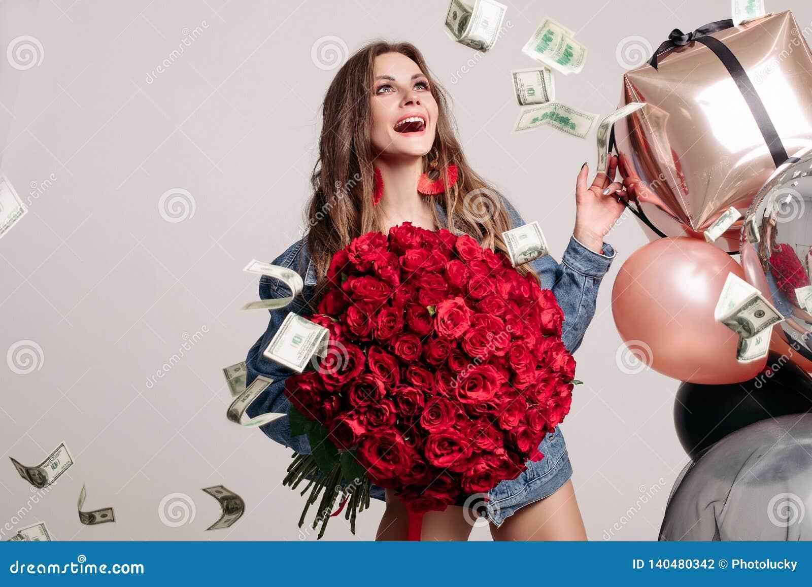 Grappige vrouw die luid terwijl geld die rond vallen lachen