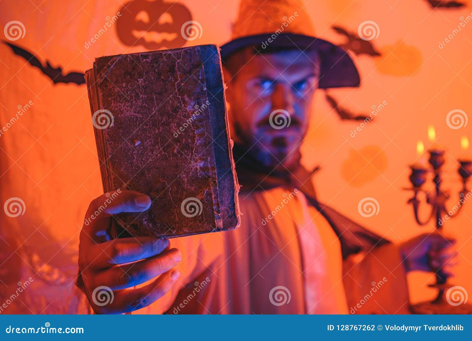 Grappige wijze tovenaar op een Halloween-achtergrond Tovenaar, tovenaar, tovenaar Knappe mens in de hoed van het tovenaarskostuum