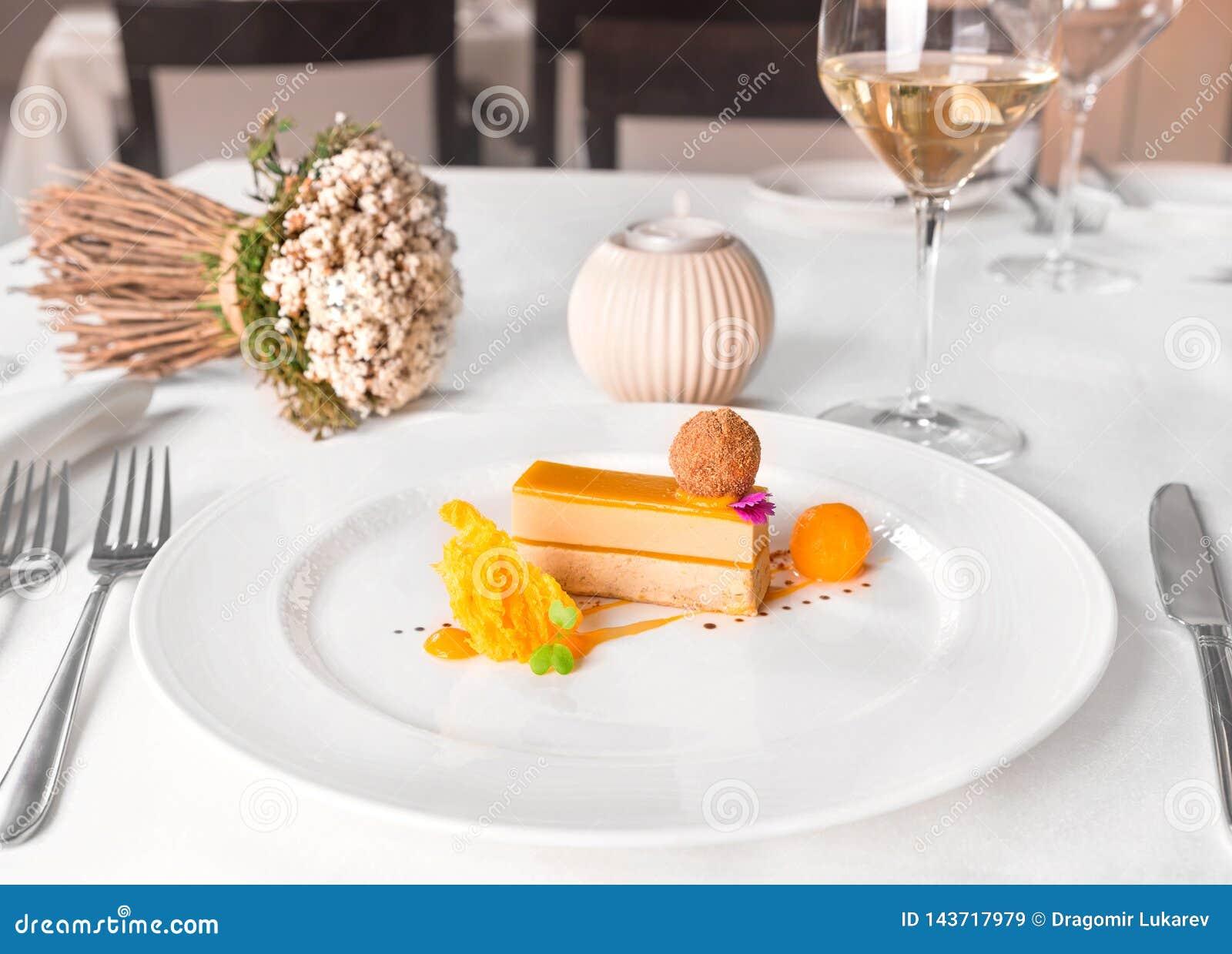 Gras y mango del foie de los Delis con la copa de vino blanca en una tabla del restaurante