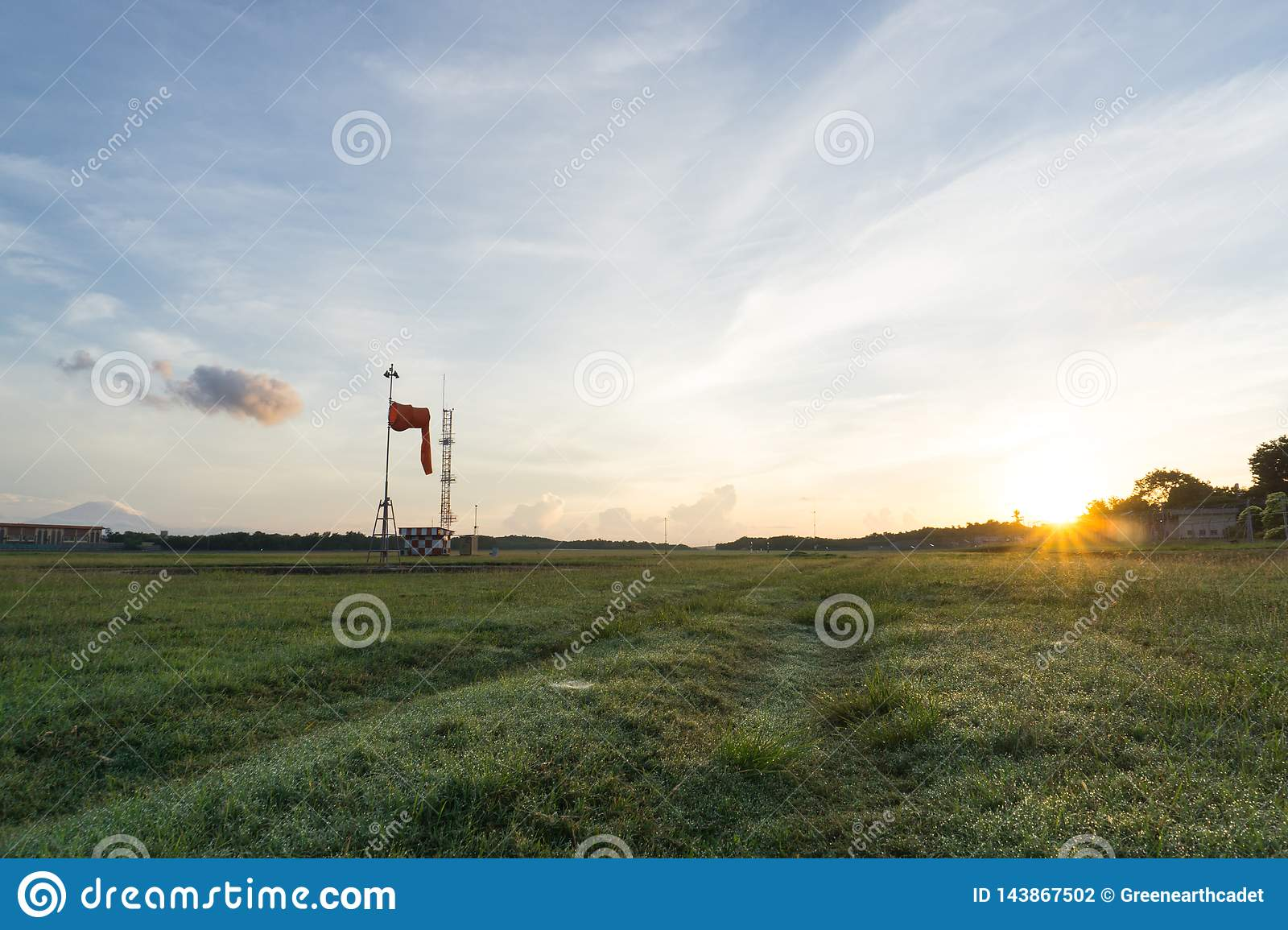 Grass field with sunrise and blue sky background
