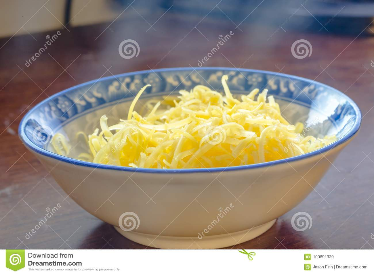 Grated mozzarella and cheddar cheese in white bowl over wooden