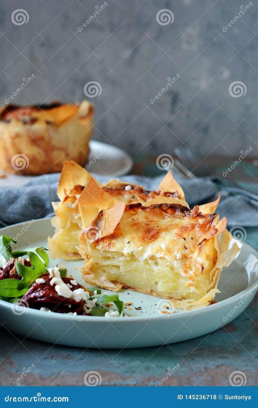 Gratin da batata cozido na massa do filo, com a crosta friável do queijo e com uma salada da rúcula, de tomates sol-secados e d